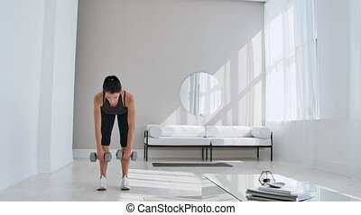 A young athletic woman in a bright apartment performs a ...