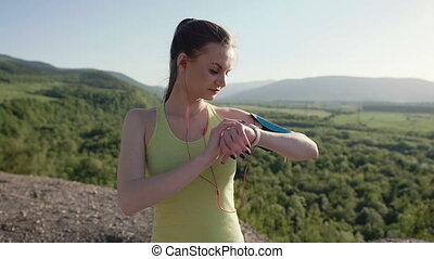 A young athletic woman who running in the fresh air in the mountains at sunset listening to music with earphones from her smartphone. Healthy lifestyle
