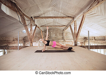 A young athletic woman working out on an abandoned construction site