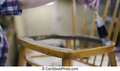 A young attractive carpenter is restoring the wooden chair.