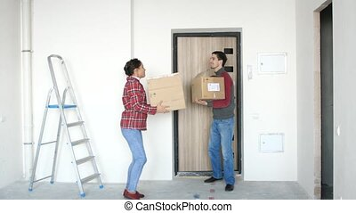 A young attractive couple moving into a new home with boxes. A joyful couple is dancing with boxes on the doorstep. 3840x2160, 4k