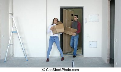 A young attractive couple moving into a new home with boxes. A joyful couple is hugging and standing on the doorstep. 3840x2160, 4k