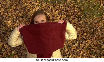 A young attractive girl, in the autumn Park, looks at the camera, smiles and touches the scarf.
