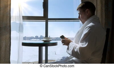 A young, attractive man, a business man sitting at a table by the window, drinks tea, coffee and writes a text message on his mobile phone. The wife comes to her husband and kisses him.