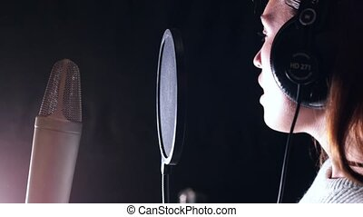 A young attractive woman in recording studio