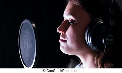 A young attractive woman in recording studio standing near a...