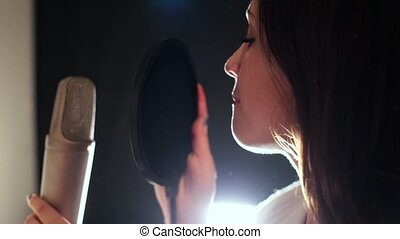A young attractive woman singing in recording studio. Bright light