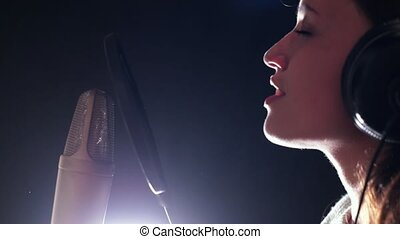 A young attractive woman singing in recording studio,...