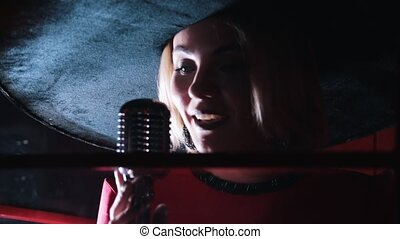 A young attractive woman singing in the studio