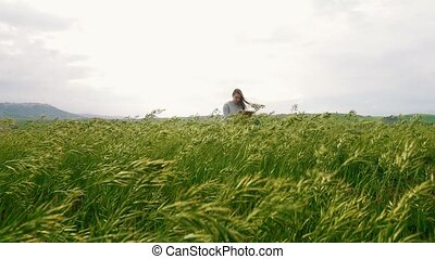 A young attractive woman sits on a hillside and draw. and...