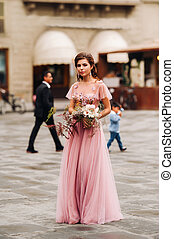 A young beautiful bride stands at the center of the Old city of Florence in Italy. Bride in a beautiful pink dress with a bouquet in Tuscany.Italy.