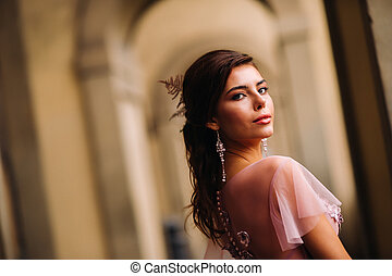 A young beautiful bride stands at the center of the Old city of Florence in Italy. Bride in a beautiful pink dress in Tuscany.Italy.