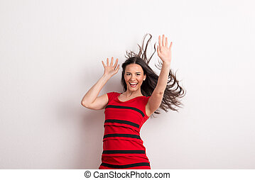 A young beautiful delighted woman with black and red t-shirt in a studio.