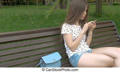 A young beautiful girl does not know that her wallet was stolen. She listens to music on the smartphone. The thief stole the purse from the bag. Close-up