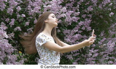 A young beautiful girl is enjoying a beautiful lilac bush. Makes a selfie on a smartphone.