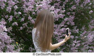 A young beautiful girl is enjoying a beautiful lilac bush. Makes a selfie on a smartphone. Summer day, good mood.