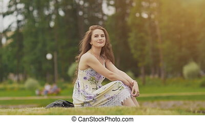 A young beautiful girl with long hair in a summer dress is sitting on a green grass in the park and sensually smiles into the camera, touching her curly hair. Summer. Delight. Recreation. Youth.