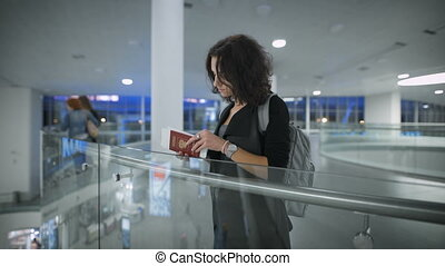 A young beautiful lady is looking at her passport at the airport