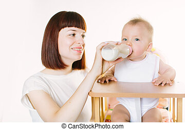 A young beautiful mother feeds a baby from a bottle. The child is sitting on a chair on a white background