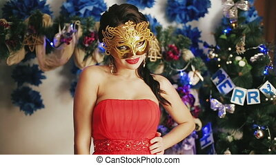 A young beautiful sexy girl in the mask near Christmas tree