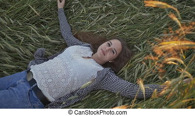 A young beautiful teenage girl lies in a wheat field on a soft sunset.