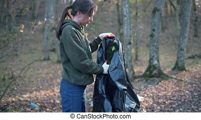 A young beautiful woman collects a plastic in the autumn forest. Activist with black garbage bag in nature in the park