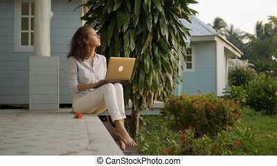 A young beautiful woman freelancer is sitting on the terrace with a laptop in the background of her home