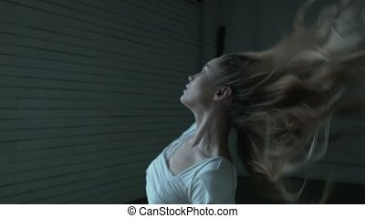 A young beautiful woman in a white dress on a dark background turns in a dance and jumps like a ballerina. The blonde opens her hair during the spin.