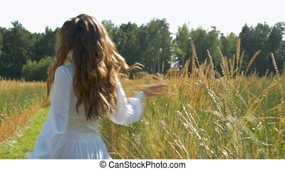 A young beautiful woman in a white dress is spinning on a field with wheat. Slow motion.
