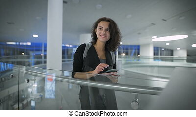 A young beautiful woman is checking news in her phone and smiling