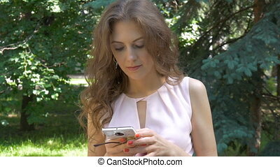 A young beautiful woman is picking up sms on a smartphone.
