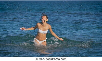 A young beautiful woman jumping in the sea