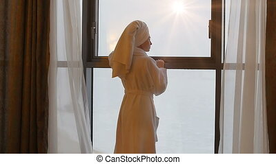 A young, beautiful woman looks out the window early in the morning.