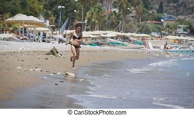 A young beautiful woman running at a sea
