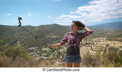 A young beautiful woman using extreme camera at incredible landscapes in Cyprus. Awesome view from the top of the mountain