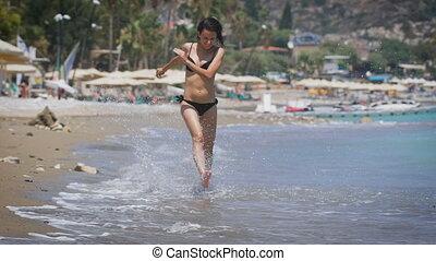A young beautiful woman wearing black bikini running at a...