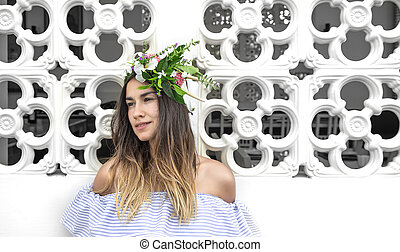 A young beautiful woman with a wreath of flowers on her head.