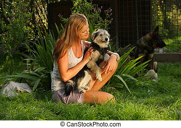 A young beautiful woman with blonde hair is holding lovingly a stray dog in her arms  in a backyard garden with green grass