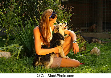A young beautiful woman with blonde hair is holding lovingly a stray dog in her arms  in a backyard