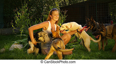 A young beautiful woman with blonde hair is playing with dogs in a backyard with green grass