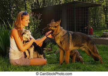A young beautiful woman with blonde hair is stroking a german shepperd dog in a backyard with green grass