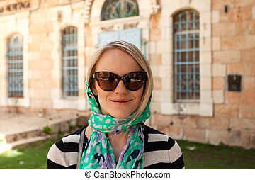 A young believing woman stands in a scarf near the entrance to a church in Jerusalem, Israel