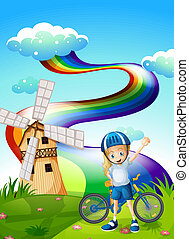 A young biker at the hilltop with a windmill and a rainbow