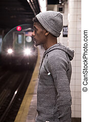 A young, black male waits for a NYC subway train