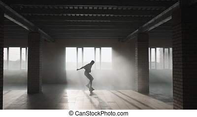 A young black man practices football dribbling in an underground parking lot in the sunlight in slow motion. Run and drive the soccer ball. High quality 4k footage