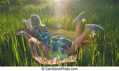 A young blond girl laying on blanket in a grass filed and...