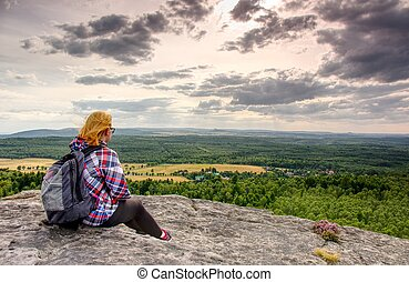 A young blond girl sit on peak and enjoy sun. Woman hiker