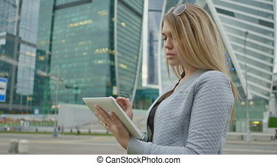 A young blond girl uses a tablet on a background of skyscrapers downtown.