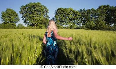 A young blond girl wear blue dress running through a wheat field. Sunset flares come up through the wheat. Slow motion, Rear view. Steadycam movement