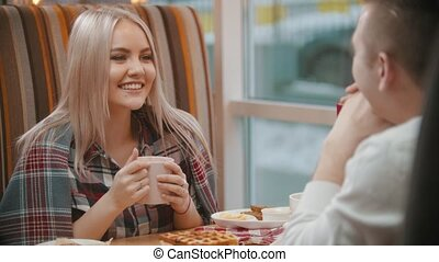 A young blond woman drinks coffee and talking with her boyfriend in cafe